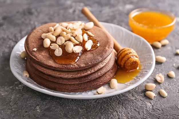 Plaat met smakelijke chocoladepannekoeken, pinda's en honing op grijze lijst