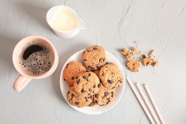 Plaat met smakelijke chocolate chip cookies en kopje koffie op grijze achtergrond, bovenaanzicht