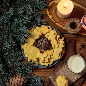 Plaat met smakelijke kerstkoekjes, kaars en cadeau op houten tafel. bovenaanzicht instagram plein
