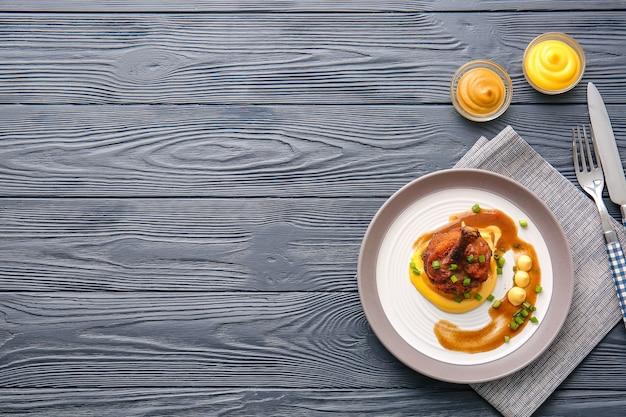 Plaat met smakelijke kippenlolly op donkere houten oppervlakte