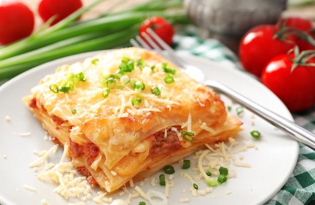 Plaat met smakelijke lasagne op tafel
