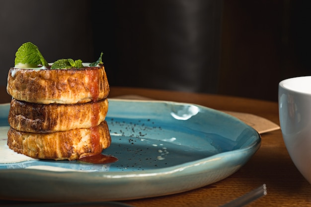 Plaat met smakelijke pannenkoeken op houten tafel