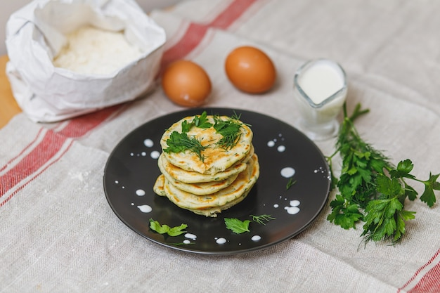 Plaat met stapel vers gebakken pannenkoeken en ingridients op tafel