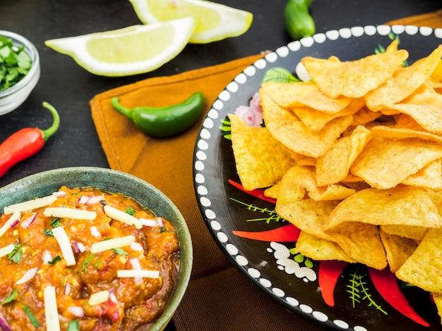 Plaat met taco's in de buurt van kopje garnituur en groenten