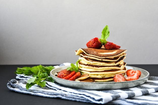 Plaat met traditionele pannenkoeken en tiny pancake cereal met aardbeien en muntblaadjes op een donkere achtergrond. trendy eten. mini-ontbijtgranenpannenkoekjes