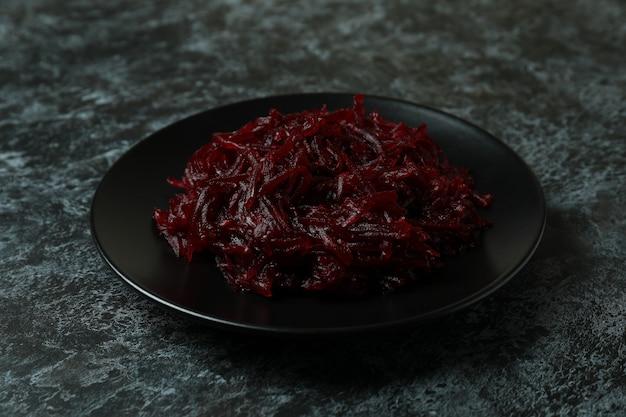 Plaat met verse bietensalade op zwarte rokerige lijst