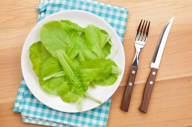 Plaat met verse salade, mes en vork. dieetvoeding op houten tafel met kopieerruimte