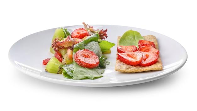 Plaat met verse smakelijke salade op witte achtergrond