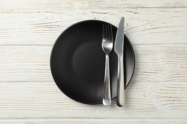 Plaat met vork en mes op houten achtergrond, bovenaanzicht