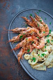 Plaat met zeevruchten, grote garnalen en inktvis, vis menu in het restaurant