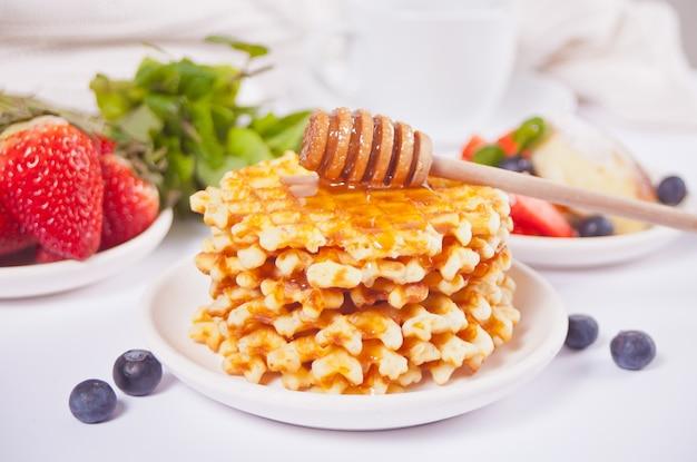 Plaat met zoete smakelijke wafels met honing, bessen, kopje thee