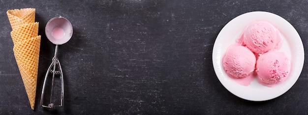 Plaat van aardbeienijslepels en wafelkegels op donker