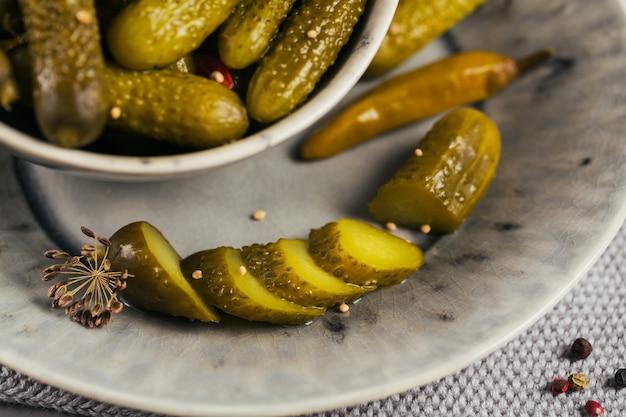 Plaat van augurken, ingelegde komkommers op een grijze achtergrond. schoon eten, vegetarisch voedselconcept