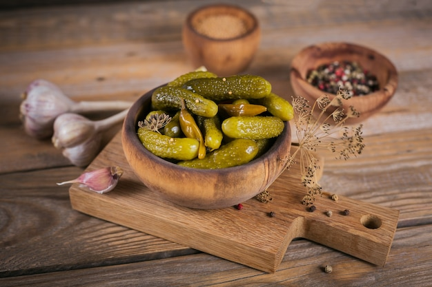 Plaat van augurken, ingelegde komkommers op een rustieke houten achtergrond. schoon eten, vegetarisch voedselconcept