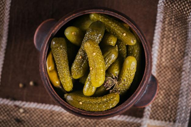 Plaat van augurken, ingelegde komkommers op rustieke houten achtergrond. schoon eten, vegetarisch voedselconcept. bovenaanzicht, close-up