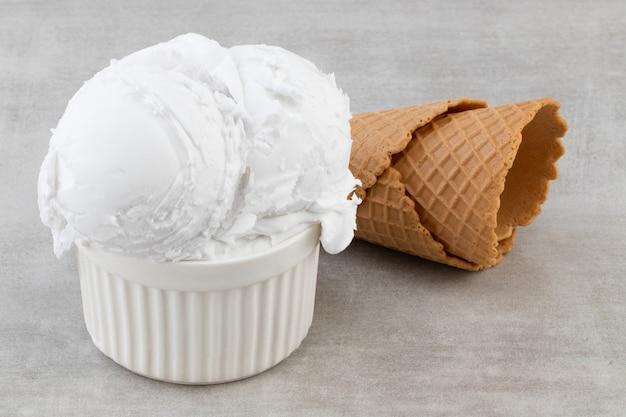 Plaat van bolletjes vanille-ijs en wafel kegels.
