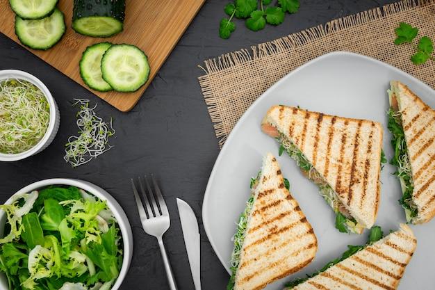 Plaat van broodjes met salade en komkommer