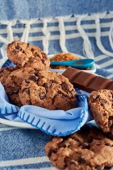 Plaat van cacaokoekjes, bruine rietsuiker en chocolade, met blauwe tinten op servet, houten tafel, tafelkleed en lepel