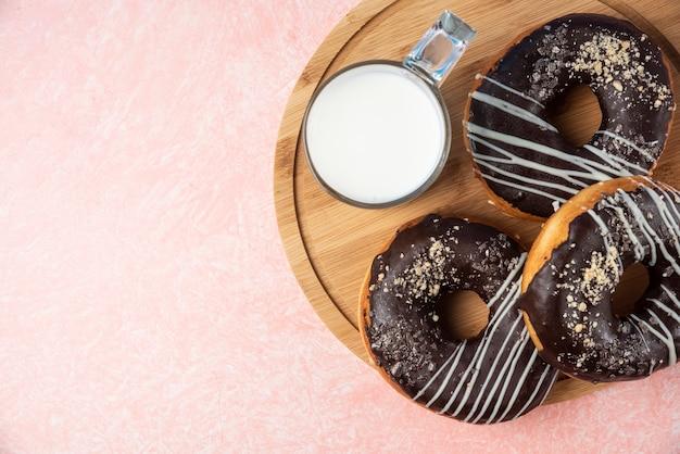 Plaat van chocolade donuts met een glas melk op roze achtergrond.