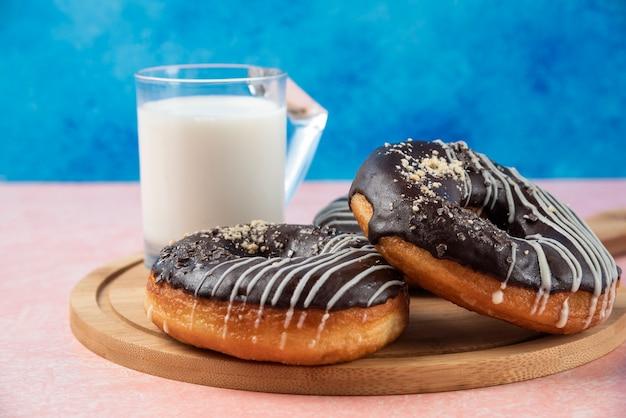 Plaat van chocolade donuts met een glas melk op roze tafel.