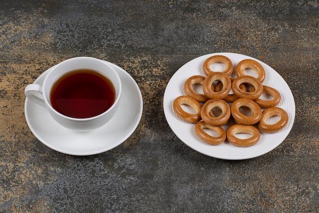 Plaat van crackers en kopje thee op marmer.