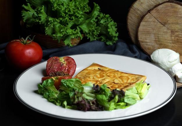 Plaat van crêpe met kaas geserveerd met slasalade en gegrilde tomaat