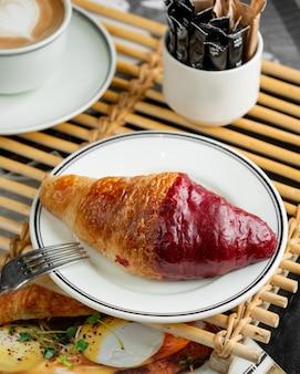 Plaat van croissant half bedekt met aardbeiensiroop