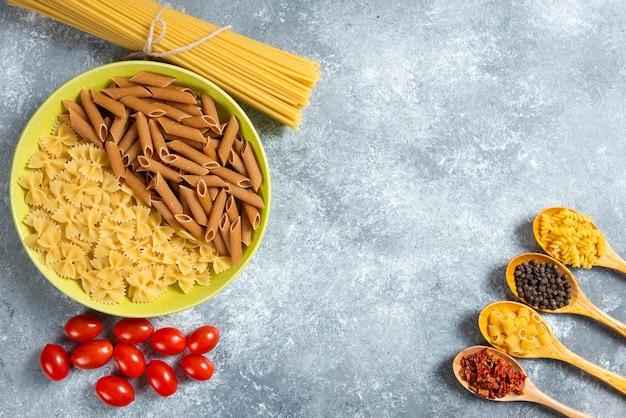 Plaat van diverse deegwaren, spaghetti en tomaten op marmeren achtergrond.