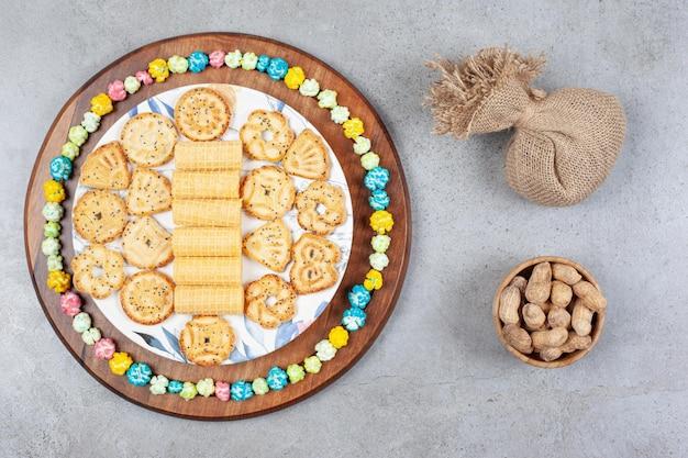 Plaat van diverse koekjes omringd door popcorn snoep op een houten bord naast een zak en een kom met pinda's op marmeren oppervlak.