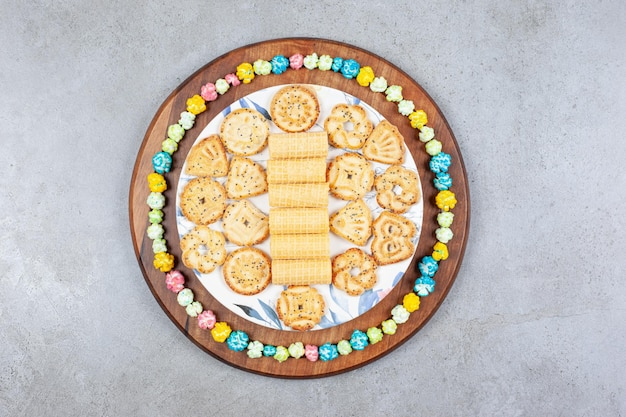 Plaat van diverse koekjes omringd door popcorn snoep op houten bord op marmeren oppervlak. Gratis Foto