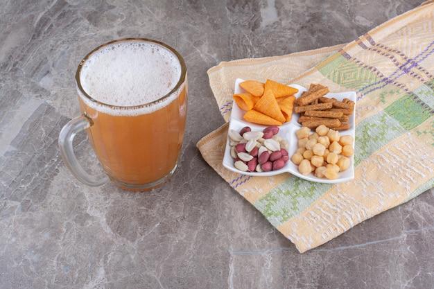 Plaat van diverse snacks en bier op marmeren oppervlak