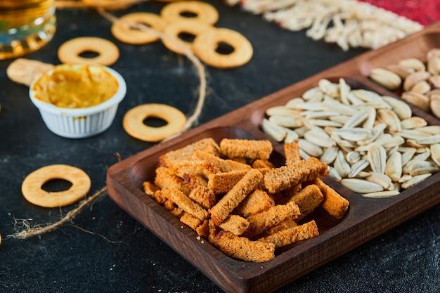 Plaat van diverse snacks en crackers op donkere tafel.
