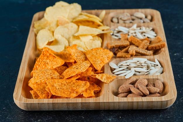 Plaat van diverse snacks op een donkere tafel.
