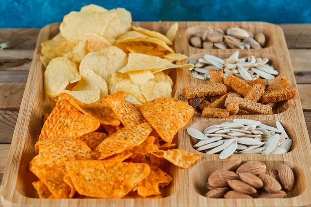 Plaat van diverse snacks op een houten tafel. chips, crackers, amandelen, pistachenoten, zonnebloempitten.