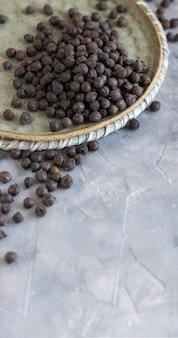 Plaat van droge zwarte kikkererwten uit apulië en basilicata in italië op grijze tafel met kopieerruimte, close-up