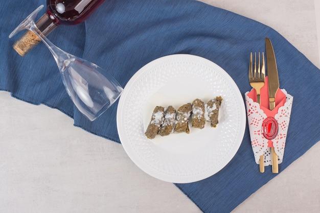 Plaat van druivenbladeren dolma, glas en bestek.