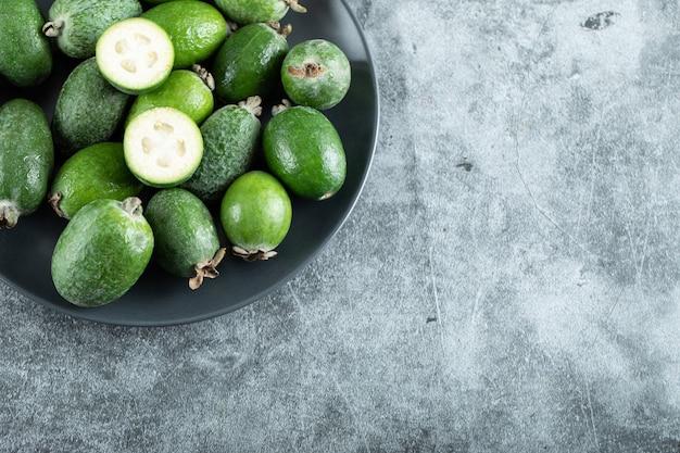Plaat van feijoa-vruchten op marmer.