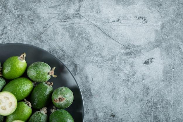 Plaat van feijoavruchten op marmeren achtergrond. hoge kwaliteit foto