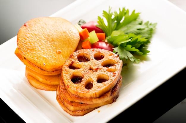 Plaat van gebakken aardappelen en groenten
