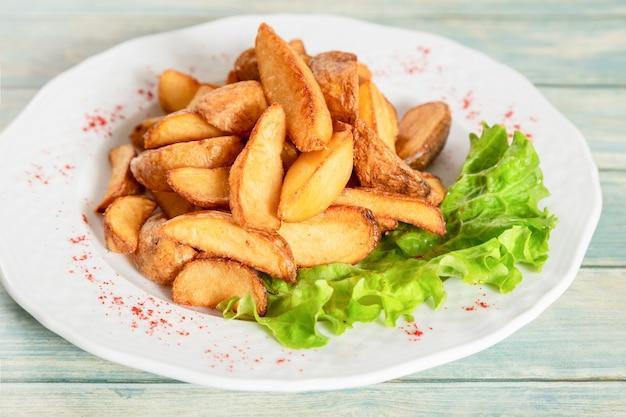 Plaat van gebakken aardappeltjes met sla en paprika