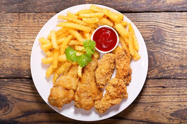 Plaat van gebakken kip met frietjes op een houten tafel
