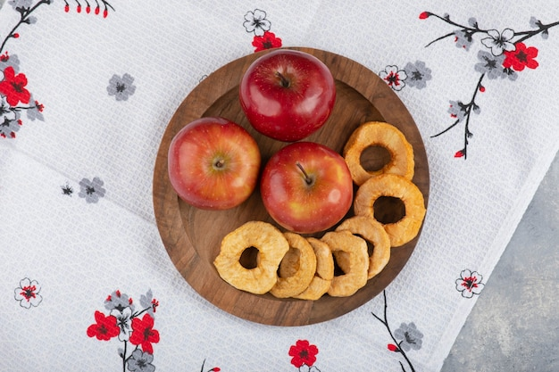 Plaat van gedroogde appelringen en verse rode appels op wit tafellaken.
