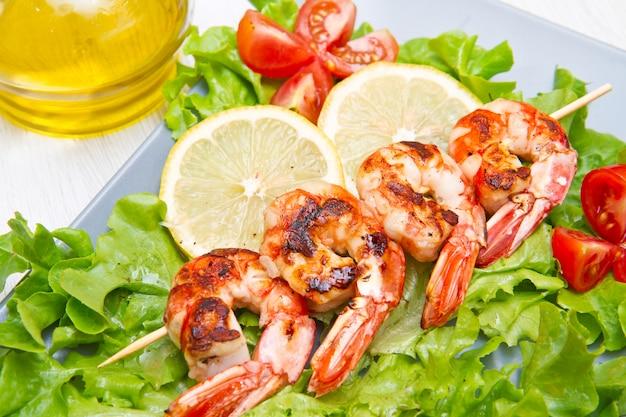 Plaat van gegrilde garnalen met salade en cherrytomaatjes