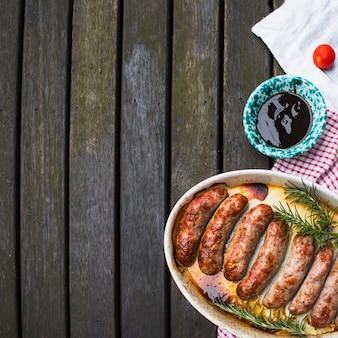 Plaat van gegrilde worstjes geserveerd met saus