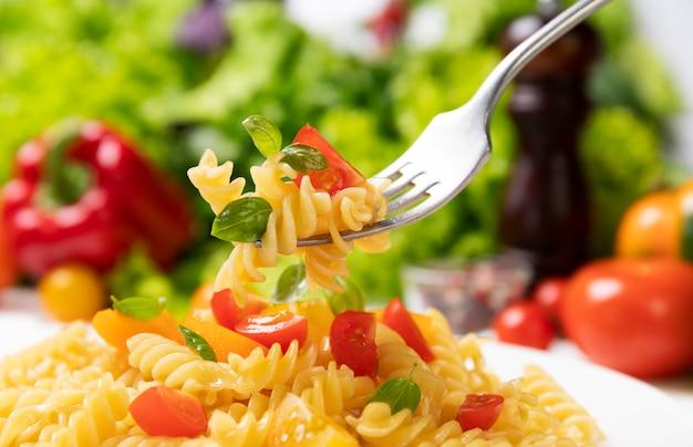 Plaat van gekookte italiaanse fusilli pasta met tomaten en basilicum