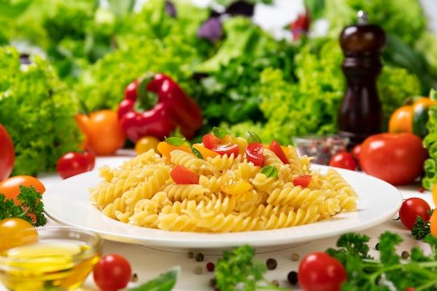 Plaat van gekookte italiaanse fusillideegwaren met tomaten en basilicumbladeren