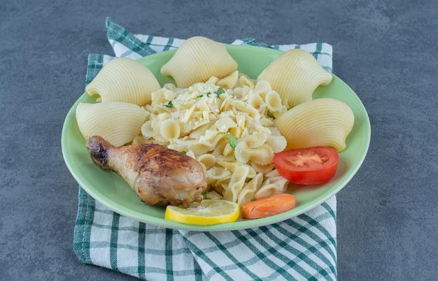 Plaat van gekookte pasta en kip drumstick op stenen oppervlak.