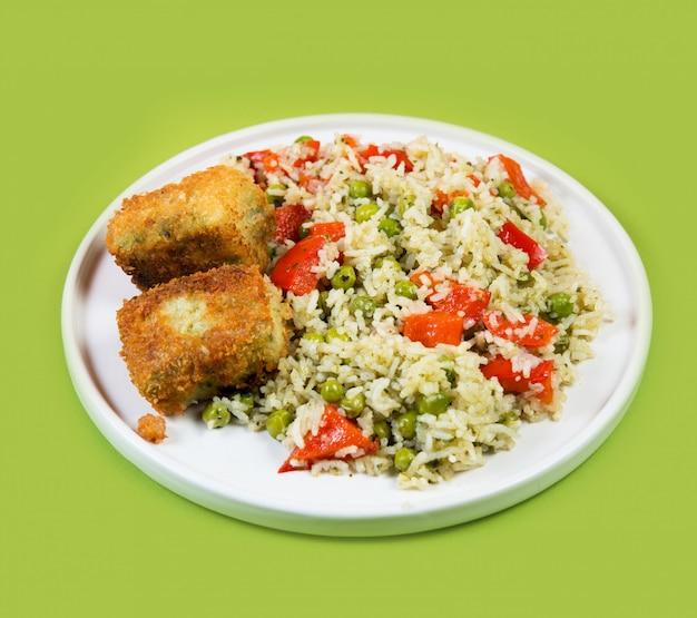 Plaat van gekookte rijst met groenten en gebraden vissen op een achtergrond van pasteltrendi, aziatisch voedsel