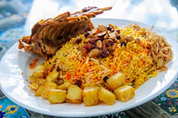 Plaat van gele rijst gegarneerd met schapenvlees en aardappelen.