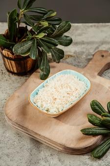 Plaat van geraspte kaas op de snijplank